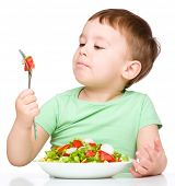 stock photo of little boys only  - Cute little boy eats vegetable salad using fork - JPG