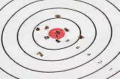 picture of bullet  - Close up of a shooting target with bullet holes in and around the red bullseye in the center - JPG