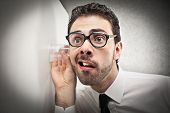stock photo of nerd  - curious businessman listens with glass leaning against the wall - JPG