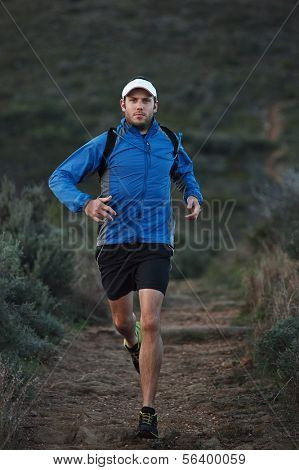 ultra marathon trail runner training in mountains for fitness and exercise wearing windbreaker