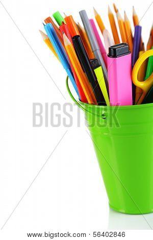 Lápis coloridos e outro art suprimentos no balde isolado no branco