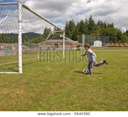 Little Boy In Cowboy Boots Kicking Soccer Ball