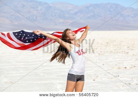 USA flag - woman athlete showing american flag. US sport athlete winner cheering waving stars and stripes outdoors in desert nature. Beautiful cheering happy young multicultural girl joyful excited.