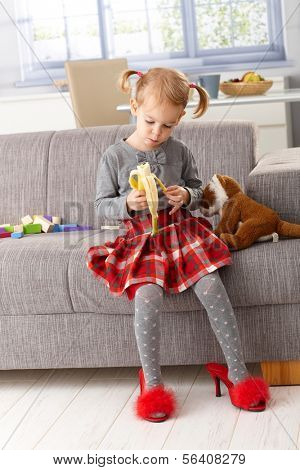 3 year old little girl eating banana at home, sitting on sofa, wearing high heel red slippers.