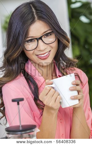 Beautiful young Asian Chinese woman or girl in geek glasses at home in her kitchen smiling and drinking a cup or mug of coffee