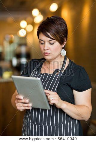 Beautiful female owner using digital tablet in coffee shop