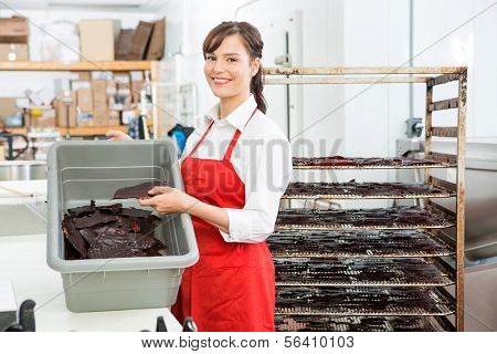 Portrait of beautiful female worker holding beef jerky and basket while standing at butcher's shop