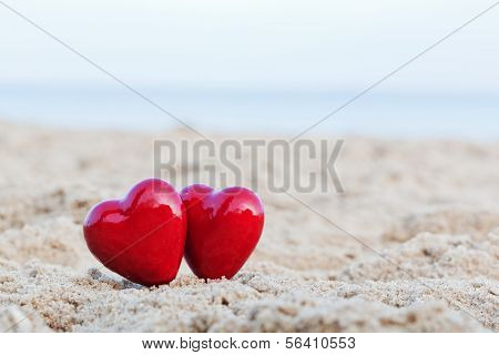 Two red hearts on the beach symbolizing love, Valentine's Day, romantic couple. Calm ocean in the background