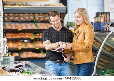 Caucasian couple checking ingredients of product at butcher's shop