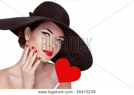 Valentine's Day. Beautiful Woman With Heart In Her Hand Wearing In Elegant Hat. Makeup. Manicured Na