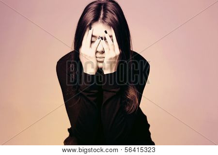 Black and white photo of a depressed young woman with hands over her head