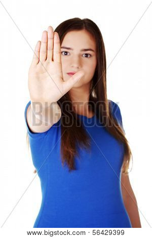 Beautiful casual woman showing stop gesture. Isolated on white.