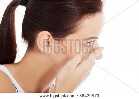 Young woman is putting eye lens.  Isolated on white.