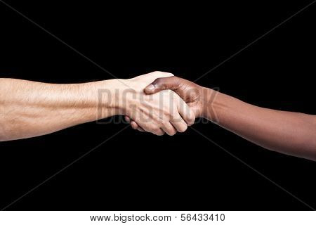 Handshake between african and a caucasian man against dark background