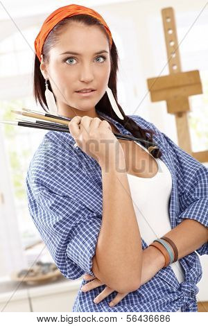 Portrait of beautiful girl with painter brushes handheld, standing at canvas stand,