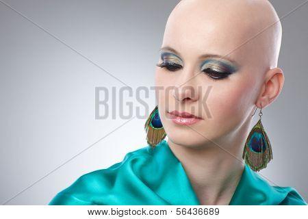Beauty portrait of bald woman in turquoise silk dress