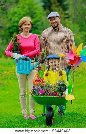 Gardening, planting - happy family with wheelbarrow working in the garden