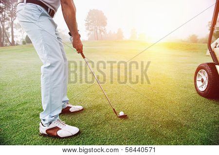 Golf approach shot with iron from fairway at sunrise poster