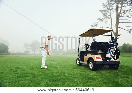 golfer in fairway with cart playing shot towards green