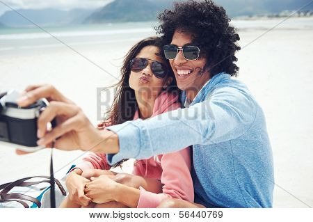 couple taking selfie self portrait at the beach with retro hipster camera