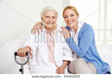 Family with happy senior woman at home sitting on the bed