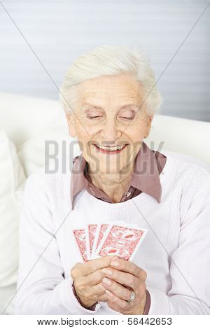 Old woman playing poker with four cards on her hand