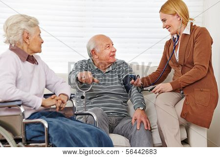 Woman measuring blood pressure on her senior parents at home