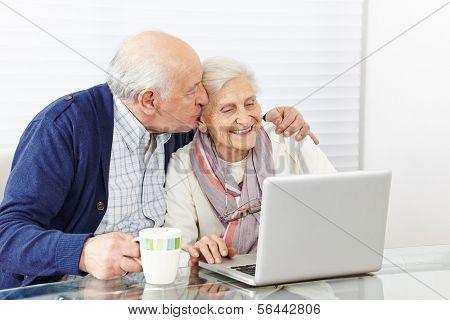 Man kissing happy senior woman at the computer on the cheek