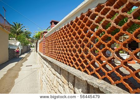 Fence made of decorative brick and stone in Susak, Croatia.