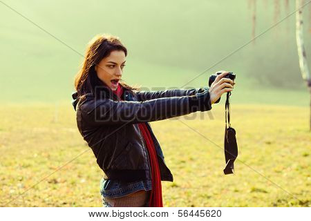 young modern girl in casual clothes take a selfportrait with camera