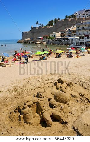 PENISCOLA, SPAIN - JULY, 26: Sand sculpture and bathers in North Beach, facing the castle, on July 26, 2013 in Peniscola, Spain, a typical summer destination in the North of the Valencian Community
