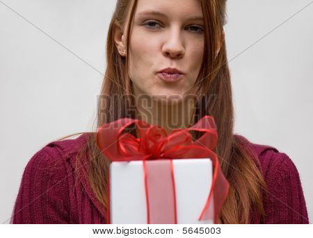 Young Woman Puckering Lips With A Gift