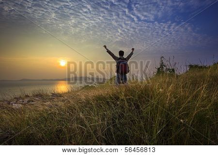 young man standing and rising hand as victory on grass hill looking to sun above sea horizontal with