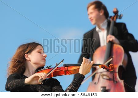 Violinist And Violoncellist Play Against Sky