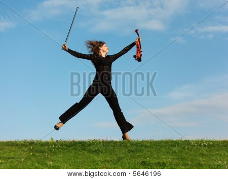 Girl With Violin Jumps On Grass Against  Sky
