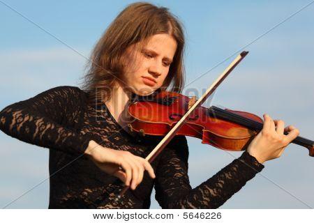 Girl Plays Violin Against  Sky