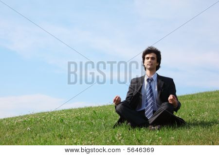 Businessman Meditates Sitting On Meadow