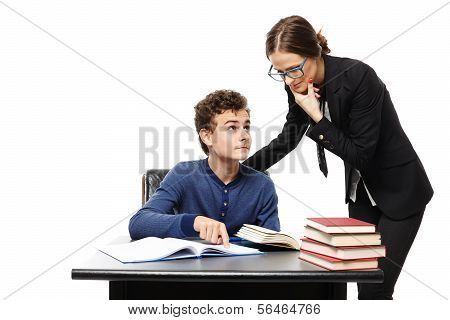 Teacher Standing Next To The Student's Desk  And The Student Pointing The Teacher Something In The B