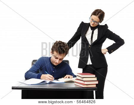 Teacher Standing Next To Student's Desk With Hand On Waist, Supervising Him