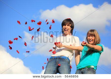 Casal jovem espalha pétalas de rosas contra Sky