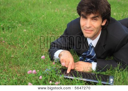 Smiling Businessman Lies On Grass With Laptop