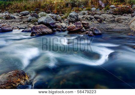 River Water Flowing Through Rocks At Dusk