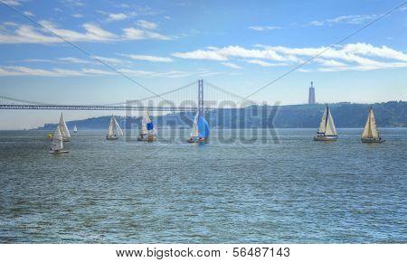 LISBON - MARCH 26: Sailing boats near the 25 de Abril Bridge above Tagus river March 26, 2009 in Lisbon, Portugal.
