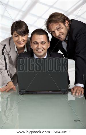 Compañeros de trabajo felices detrás de un ordenador portátil