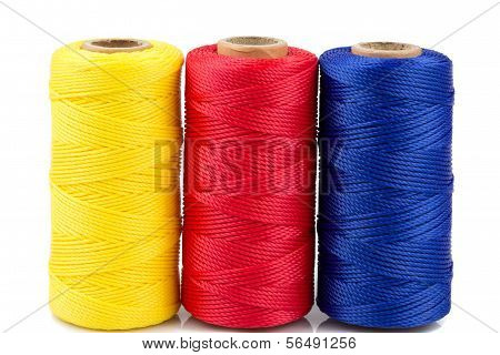 three spools of thread of different colors isolated on white background
