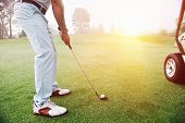 stock photo of swing  - Golf approach shot with iron from fairway at sunrise - JPG