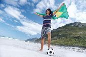 Latino Brasil football soccer fan with flag and ball on beach