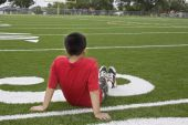 foto of little boy  - A young boy sits on a football field dreaming about his future - JPG
