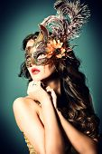 stock photo of mask  - Portrait of a beautiful young woman in a carnival mask - JPG