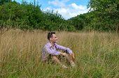 picture of lederhosen  - Young man in traditional Bavarian lederhosen relaxing in the field - JPG